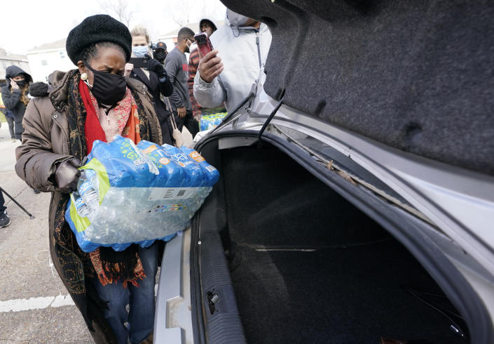 U.S. Rep. Sheila Jackson Lee, D-Texas, loads donated water into a car at a distribution site Thursday, Feb. 18, 2021, in Houston. Houston and several surrounding cities are under a boil water notice as many residents are still without running water in their homes. (AP Photo/David J. Phillip)