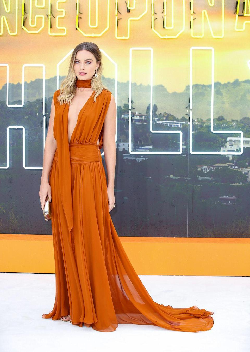<p>After a number of public appearances opting for white, Robbie switched things up to absolutely floor the red carpet of the Once Upon A Time In Hollywood London premiere in a tan-coloured Oscar de la Renta gown with a plunging neckline. She paired the dress with gold open toe strappy heeled sandals from Tabitha Simmons.</p>