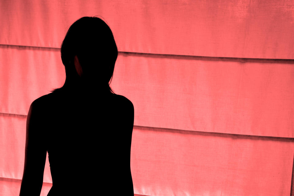 Woman in shadow in front of pink wall represents sex workers left behind in COVID-19 brothel lock down