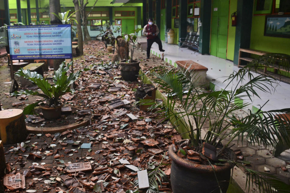 Pieces of roof tiles and other debris litter the ground at a school following an earthquake in Malang, East Java, Indonesia, Saturday, April 10, 2021. A strong earthquake damaged buildings on Indonesia's main island of Java and shook the tourist hotspot of Bali, officials said Saturday. No tsunami warnings were posted. (AP Photo/Hendra Permana)
