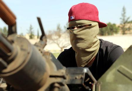 A masked member of Libyan internationally recognised pro-government forces is seen in a military vehicle on the outskirts of Tripoli, Libya April 10, 2019. REUTERS/Hani Amara
