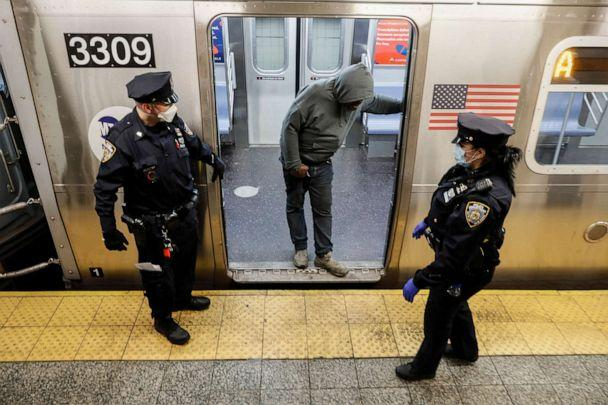 PHOTO: NYPD officers direct passengers to exit the 207th Street A-train station, April 30, 2020, in the Manhattan borough of New York. (John Minchillo/AP)