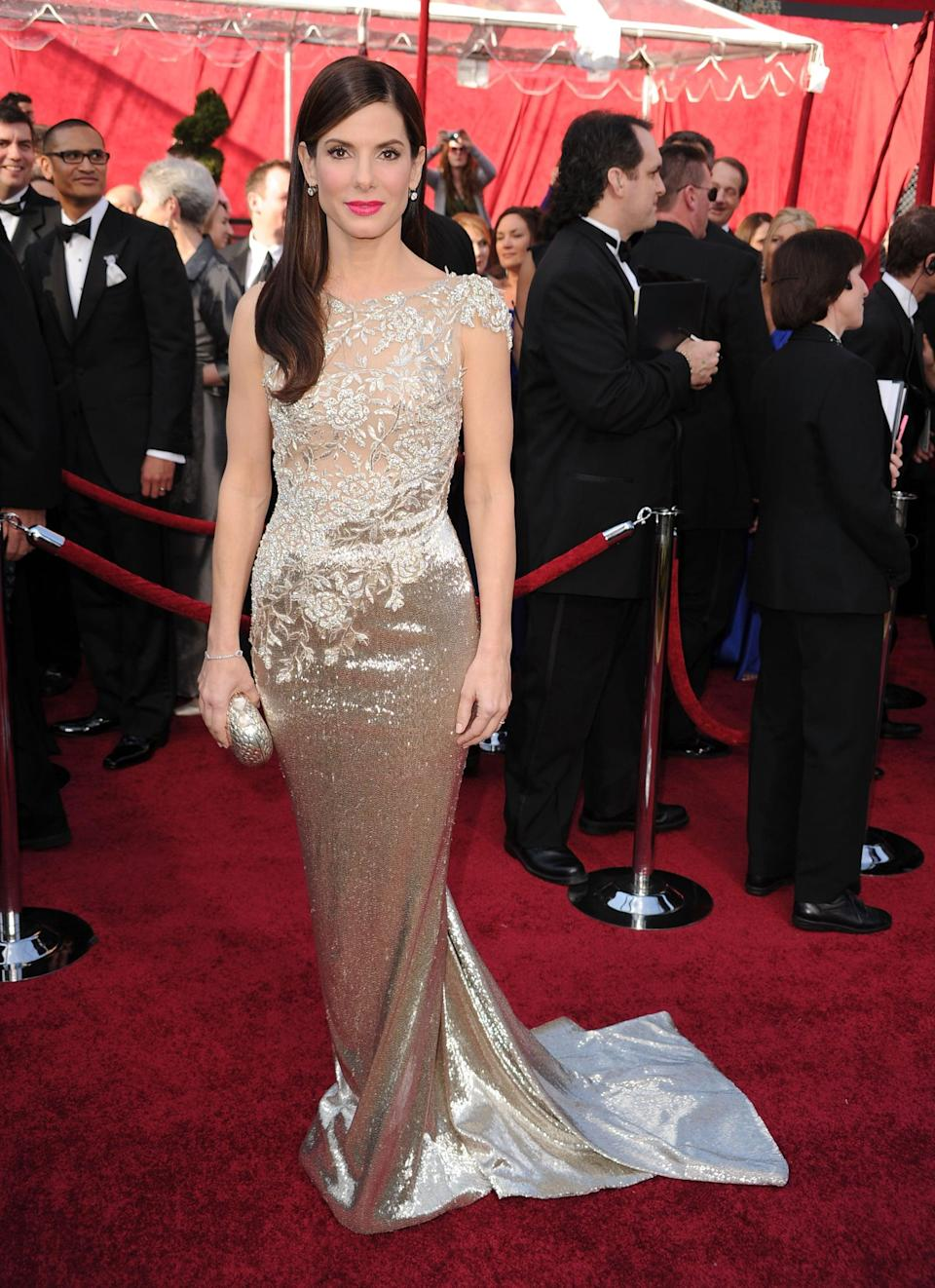 <p>Sandra looked like a winner - and become one later that evening - in this silver gown by Marchesa.</p>
