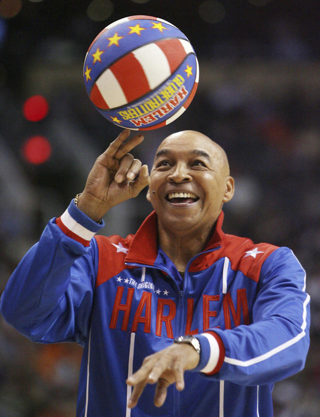 """The Harlem Globetrotters' Fred """"Curly"""" Neal performs during a timeout in the second quarter in an NBA basketball game between the Indiana Pacers and the Phoenix Suns in Phoenix. Neal, the dribbling wizard who entertained millions with the Harlem Globetrotters for parts of three decades, has died the Globetrotters announced Thursday, March 26, 2020. He was 77. Neal played for the Globetrotters from 1963-85, appearing in more than 6,000 games in 97 countries for the exhibition team known for its combination of comedy and athleticism. (AP Photo/Ross D. Franklin, File)"""