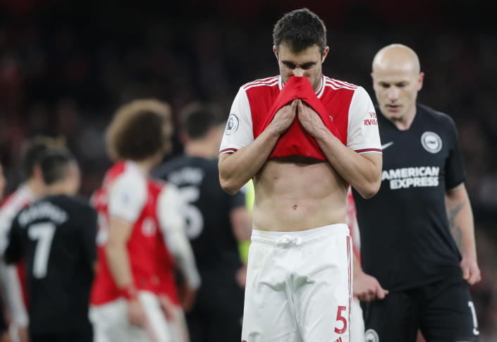 Arsenal's Sokratis Papastathopoulos wipes his face during the English Premier League soccer match between Arsenal and Brighton, at the Emirates Stadium in London, Thursday, Dec. 5, 2019. (AP Photo/Frank Augstein)