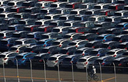 FILE PHOTO - A worker cycles past newly produced cars at an industrial port in Kawasaki, Japan, October 24, 2016. REUTERS/Kim Kyung-Hoon/File Photo