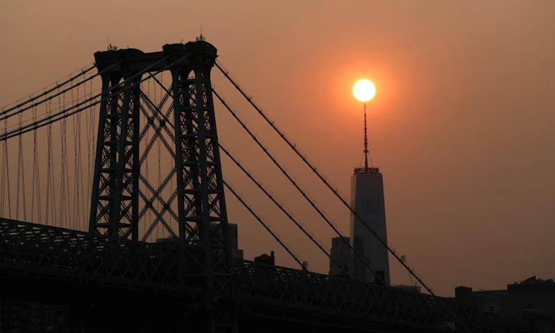 The sun sets behind the Manhattan Bridge and One World Trade Center in a haze created by smoke from the west coast wildfires this week.