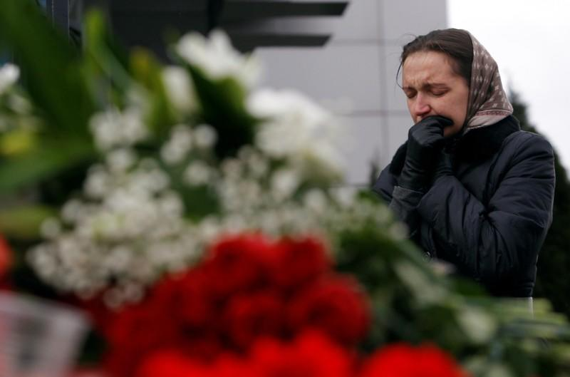 FILE PHOTO: Woman mourns near flowers left outside Kazan airport, where a Tatarstan Airlines Boeing 737 crashed