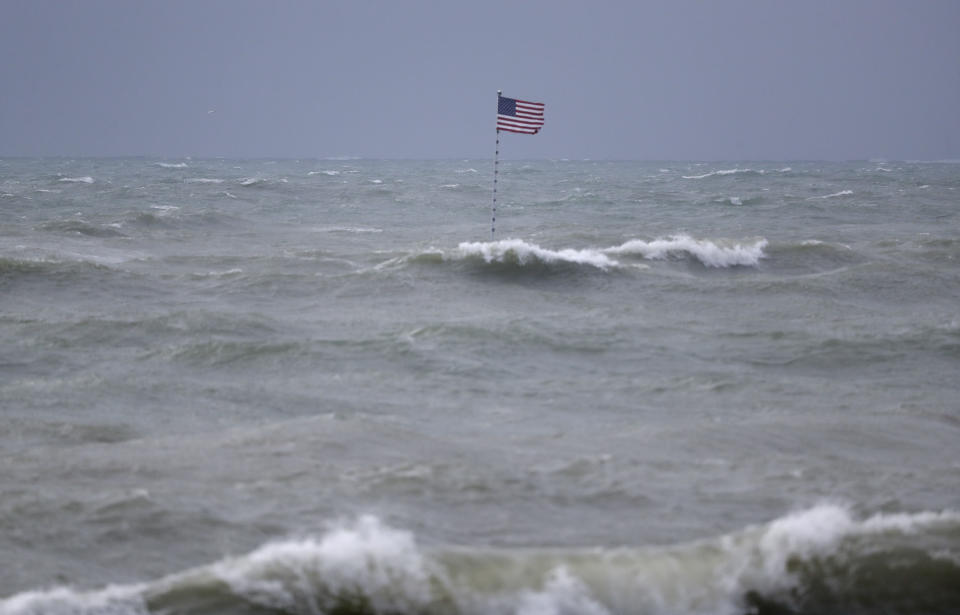 An American flag flies from the shipwreck of the Breconshire, as waves churned up by Tropical Storm Isaias crash around it, Sunday, Aug. 2, 2020, in Vero Beach, Fla. Isaias weakened from a hurricane to a tropical storm late Saturday afternoon, but was still expected to bring heavy rain and flooding as it barrels toward Florida. The Breconshire was a cargo ship that ran aground in 1894. (AP Photo/Wilfredo Lee)