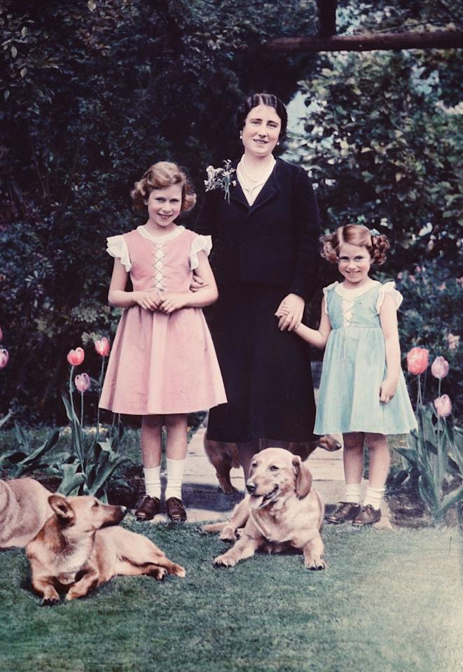 <p>Elizabeth and Margaret posed with the Queen Mother and their dogs for a portrait in the gardens at Windsor.</p>