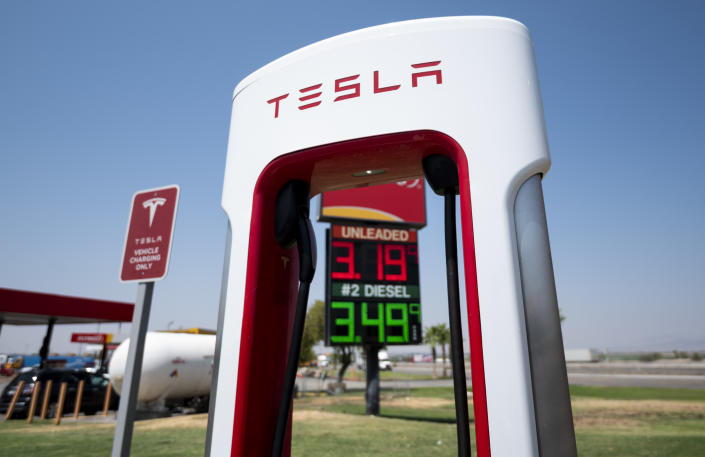 UNITED STATES - AUGUST 24: Gasoline prices are seen behind Tesla charging stations stand at an interstate highway exit in Ehrenberg, Ariz., on Tuesday, August 24, 2021. (Photo by Bill Clark/CQ-Roll Call, Inc via Getty Images)