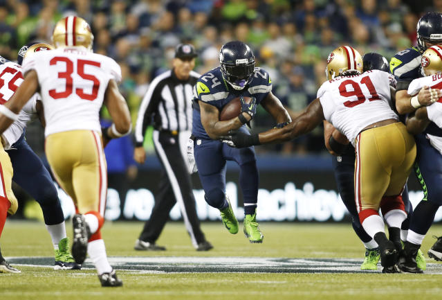 Seattle Seahawks' running back Marshawn Lynch (24) leaps as he carries the ball against San Francisco 49ers' Eric Reid (35) and Ray McDonald (91) in the first half of an NFL football game, Sunday, Sept. 15, 2013, in Seattle. (AP Photo/John Froschauer)