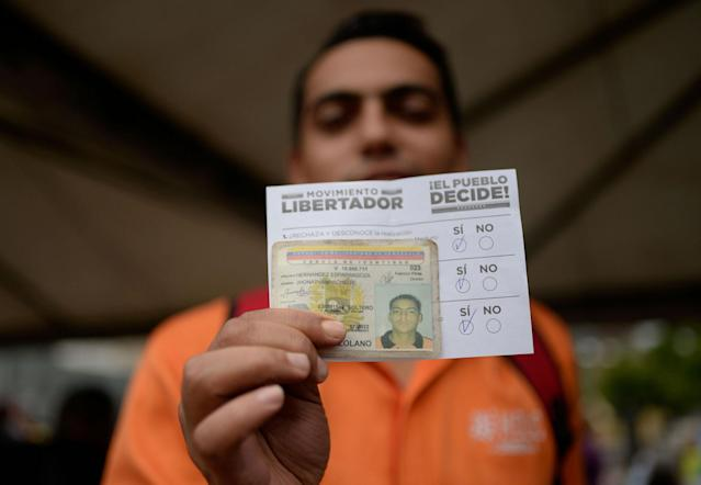 <p>A man shows his ID card and ballot at a polling station in Caracas on July 16, 2017 during an opposition-organized vote to measure public support for Venezuelan President Nicolas Maduro's plan to rewrite the constitution.<br> Authorities have refused to greenlight the vote that has been presented as an act of civil disobedience and supporters of Maduro are boycotting it. Protests against Maduro since April 1 have brought thousands to the streets demanding elections, but has also left 95 people dead, according to an official toll. (Federico Parra/AFP/Getty Images) </p>