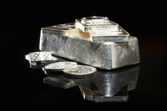 Silver bars and coins on a flat surface against a dark background.
