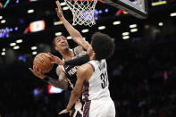 Atlanta Hawks forward John Collins (20) tries to get a shot by the defense of Brooklyn Nets center Jarrett Allen (31) during the first half of an NBA basketball game, Sunday, Jan. 12, 2020, in New York. (AP Photo/Kathy Willens)