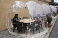 Aviva Markowitz, left, and Rivka Alter enjoy a drink in a protective bubble at the Lazy Bean Cafe in Teaneck, N.J., Thursday, Oct. 22, 2020. The bubbles have been popular with customers, both for social distancing and warmth as the weather turns colder. New Jersey's climbing number of COVID-19 cases are beginning to spread to northern counties around New York, Gov. Phil Murphy said Thursday. Essex, Union, Hudson and Bergen counties reported more than 100 new cases overnight, Murphy said, eclipsing recent hot spots in Ocean and Monmouth counties. (AP Photo/Seth Wenig)