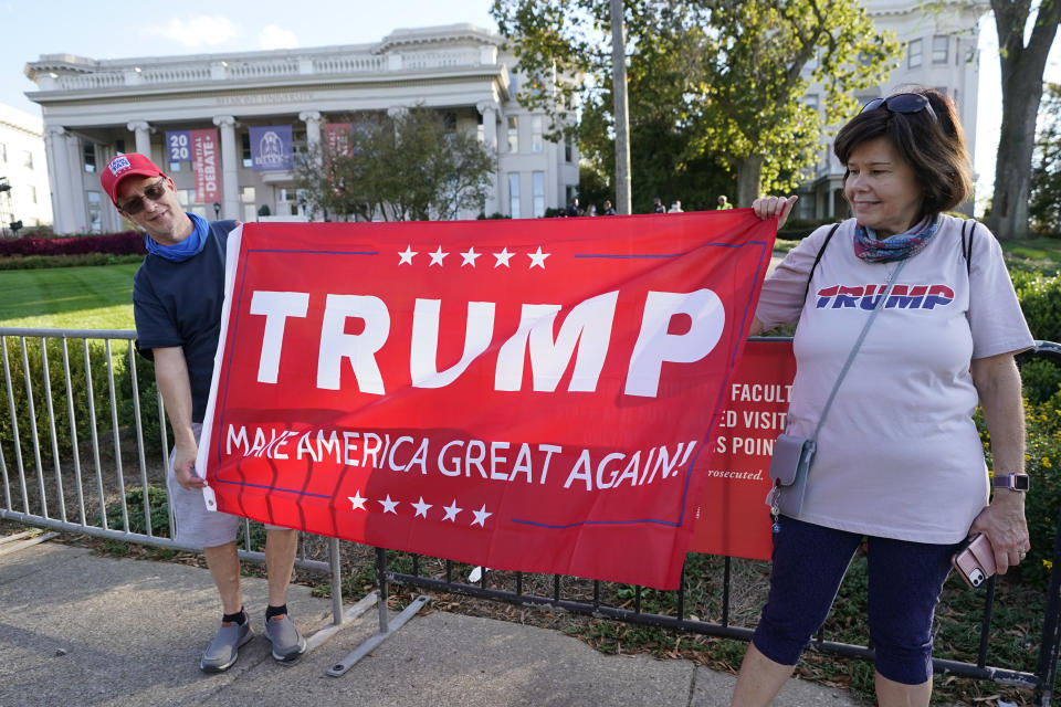 Donald Trump supporters Joe Knight, left, and his wife, Bana, hold a Trump banner in front of Belmont University Thursday, Oct. 22, 2020, in Nashville, Tenn. The second presidential debate between President Donald Trump and Democratic presidential candidate, former Vice President Joe Biden, is scheduled to be held at Belmont later in the evening. (AP Photo/Mark Humphrey)