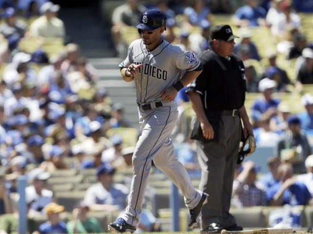 San Diego Padres' Reymond Fuentes, left, scores on a single by Alexi Amarista against the Los Angeles Dodgers in the third inning of a baseball game in Los Angeles, Sunday, Sept. 1, 2013. (AP Photo/Reed Saxon)