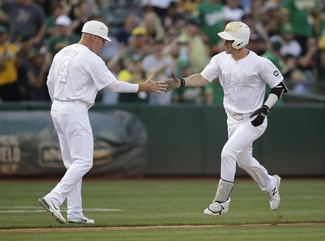 Oakland Athletics' Mark Canha, right, is congratulated by third base coach Matt Williams (4) after hitting a home run off San Francisco Giants' Madison Bumgarner during the second inning of a baseball game Saturday, Aug. 24, 2019, in Oakland, Calif. (AP Photo/Ben Margot)