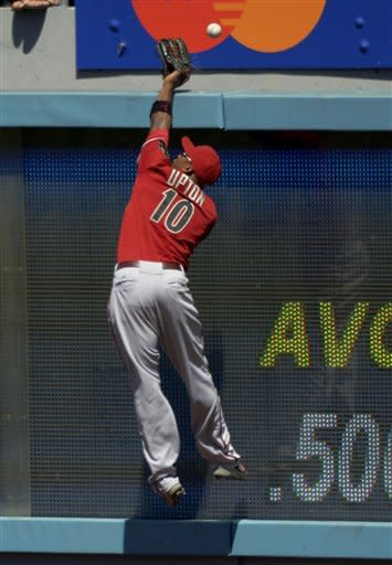 Arizona Diamondbacks right fielder Justin Upton can't reach a ball hit for a solo home run by Los Angeles Dodgers' Matt Kemp during the second inning of their baseball game, Sunday, Sept. 2, 2012, in Los Angeles. (AP Photo/Mark J. Terrill)