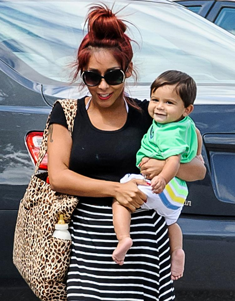 """Baby Lorenzo is less than a year old, but he proved that he already knows how to have a good time! The happy baby gave a big smile as he and mom Nicole """"Snooki"""" Polizzi arrived at a New Jersey pool for his very first swimming lesson. (8/15/2013)"""