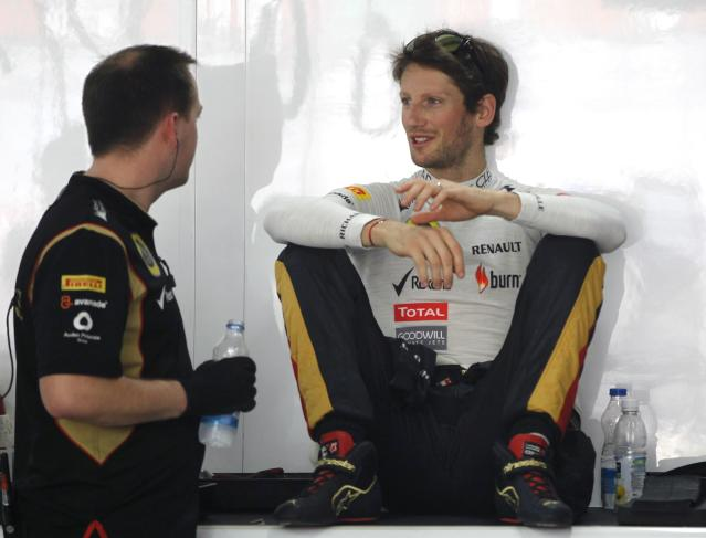 Lotus F1 Formula One driver Romain Grosjean of France (R) attends the first practice session of the Indian F1 Grand Prix at the Buddh International Circuit in Greater Noida, on the outskirts of New Delhi, October 25, 2013. REUTERS/Adnan Abidi (INDIA - Tags: SPORT MOTORSPORT F1)