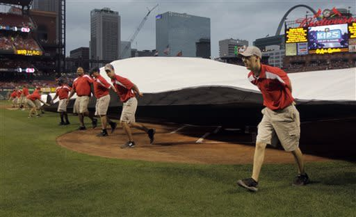 Members of the grounds crew put the tarp on the field before a baseball game between the St. Louis Cardinals and the San Francisco Giants on Friday, May 31, 2013, in St. Louis. The start of the game was delayed. (AP Photo/Jeff Roberson)