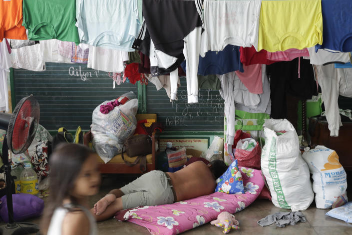 A man sleeps at a temporary evacuation center at Santa Teresita, Batangas province, southern Philippines on Thursday Jan. 16, 2020. Taal volcano belched smaller plumes of ash Thursday but shuddered continuously with earthquakes and cracked roads in nearby towns, which were blockaded by police due to fears of a bigger eruption. (AP Photo/Aaron Favila)