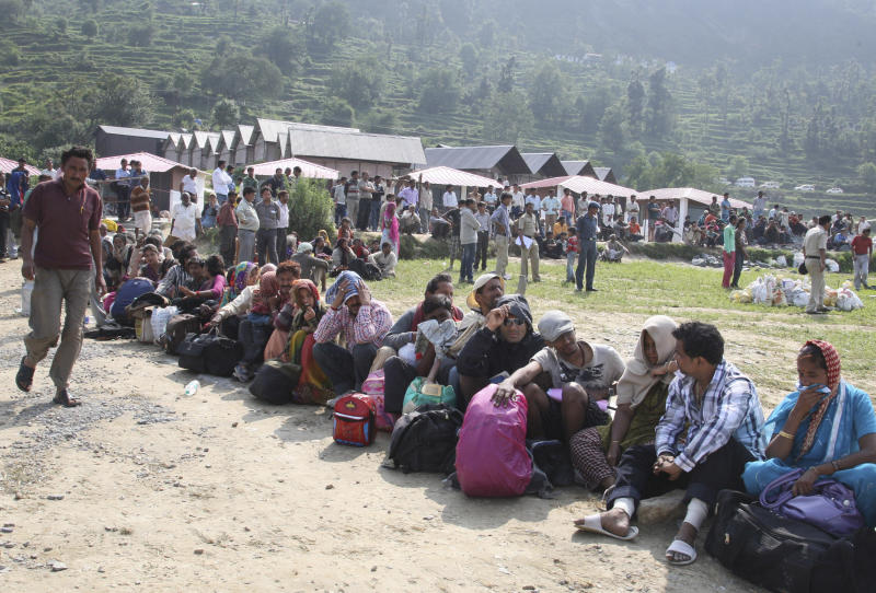 In this Friday, June 21, 2013 photo, Indian pilgrims wait to be evacuated by helicopters from the upper reaches of mountains, in Gaurikund, in northern Indian state of Uttrakhand. Officials say soldiers are working to evacuate tens of thousands of people still stranded in northern India where nearly 600 people have been killed in monsoon flooding and landslides. (AP Photo)