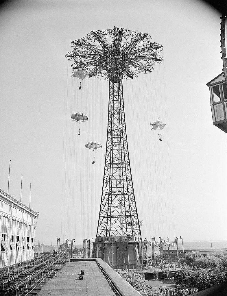 <p>Originally built for the 1939 World's Fair, the Parachute Jump eventually made its way to Steeplechase Park in 1941. Riders were strapped into a chair, lifted by cables high into the air (the tower is 200 feet tall), then dropped. Though the parachute and cables slowed riders down, the descent was still a fast one (15 seconds or so), it was more akin to free-fall.</p>