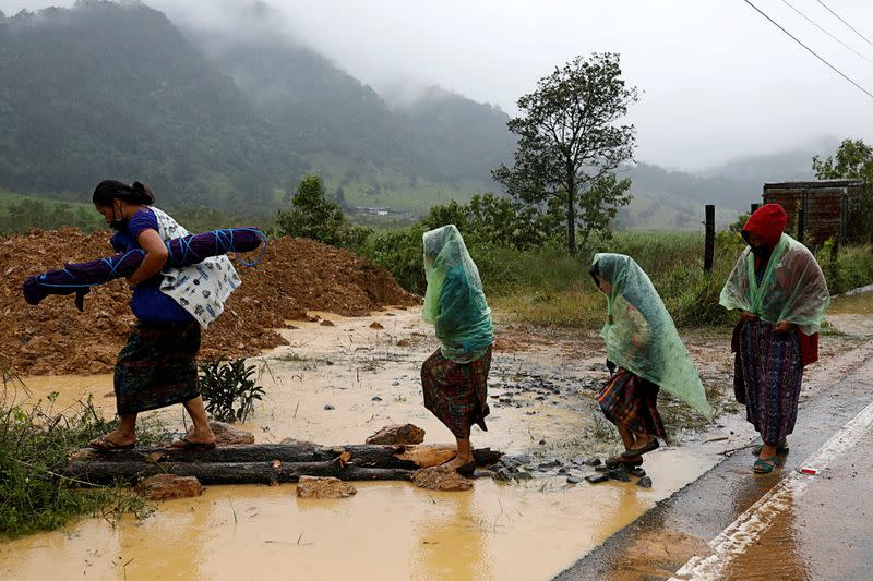 Women walk at an area affected by a mudslide after the passage of Storm Eta, in Purulha
