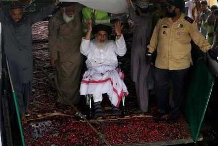 FILE PHOTO: Khadim Hussain Rizvi (on a wheelchair), leader of Tehrik-e-Labaik Pakistan islamist political party, gestures to his supporters during a campaign rally ahead of general election in Karachi, Pakistan July 1, 2018. REUTERS/Akhtar Soomro/File Photo