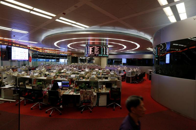 FILE PHOTO: A floor trader walks during afternoon trading at the Hong Kong Stock Exchange in Hong Kong