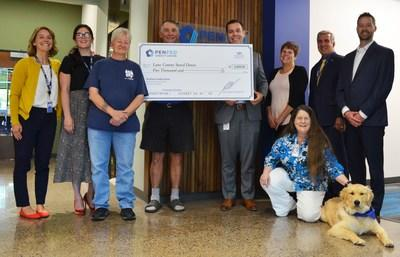 PenFed Credit Union employees and Journey, PenFed's Northwest Battle Buddies service-dog-in-training, present a donation check to Lane County Stand Down, an annual event that provides one-stop services for veterans