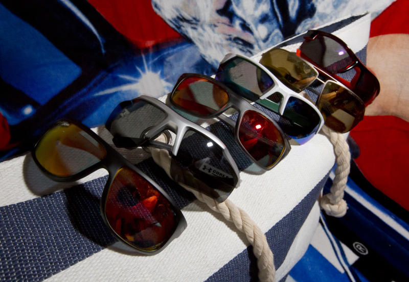 This June 18, 2013 photo shows a selection of sunglasses from Hobie and Under Armour in New York. Choosing new summer shades is more than an issue of flattering frames. There are decisions to be made about the lenses, too, and there will only be more in the future. (AP Photo/Richard Drew)