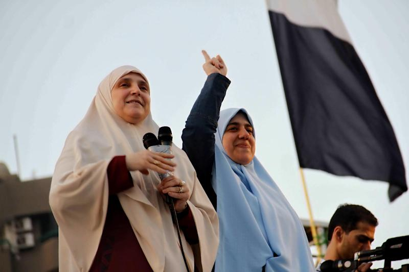 """Naglaa Mahmoud, left, the wife of Egypt's ousted President Mohammed Morsi addresses thousands of Morsi supporters gathered at a sit-in at Rabaah al-Adawiya mosque in Cairo's Nasr City suburb, Thursday, Aug. 8, 2013. Mahmoud made her first appearance since the July 3 military coup, and told Morsi's supporters Thursday to remain defiant in the face of the military-backed government's threat to clear ongoing protests, promising her husband """"is coming back, God willing."""" A daughter of Morsi holds up her finger. (AP Photo/Ravy Shaker, El Shorouk Newspaper) EGYPT OUT"""