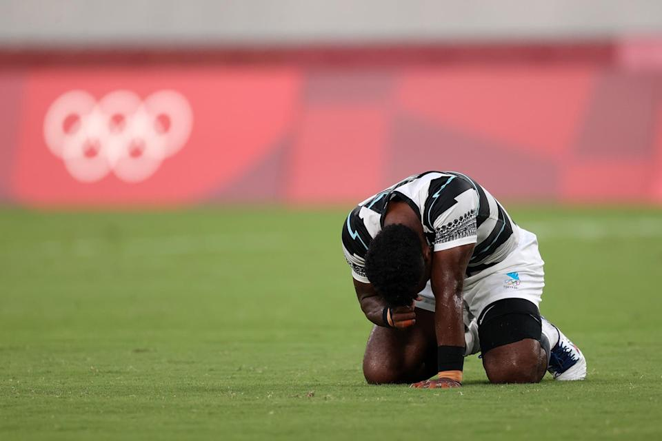 <p>Jerry Tuwai of Team Fiji falls to his knees following his team's victory in the Rugby Sevens Men's Gold Medal match between New Zealand and Fiji at Tokyo Stadium on July 28.</p>