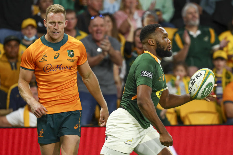 South Africa's Lukhanyo Am, right, reacts after scoring try as Australia's Reece Hodge watches during the Rugby Championship test match between the Springboks and the Wallabies in Brisbane, Australia, Saturday, Sept. 18, 2021. (AP Photo/Tertius Pickard)