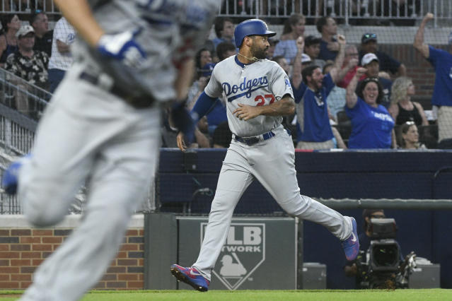 Los Angeles Dodgers' Matt Kemp, right, watches a left field line drive hit by Clayton Kershaw, left, as he runs the third base line on the way to scoring during the fourth inning of a baseball game against the Atlanta Braves, Friday, July 27, 2018, in Atlanta. (AP Photo/John Amis)