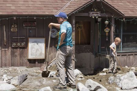 Paul McRobbie (L) holds a shovel outside a home that was damaged by a mudflow triggered by flash floods in the San Bernardino mountain community of Forest Falls, California August 4, 2014. REUTERS/Jonathan Alcorn
