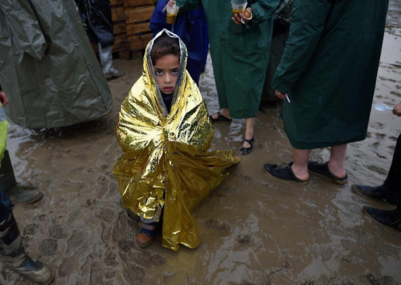 A child wrapped in a survival blanket stands by a queue for hot soup on March 13, 2016, in a makeshift camp at the Greek-Macedonian border (AFP Photo/Daniel Mihailescu)