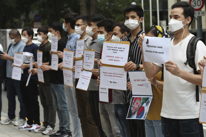 A group of Afghan nationals residing in South Korea whose family members have worked with Koreans in their home country, call for the South Korean government to rescue them during a rally outside the Foreign Ministry in Seoul, South Korea, Monday, Aug. 23, 2021.(Baek Seung-ryul/Yonhap via AP)