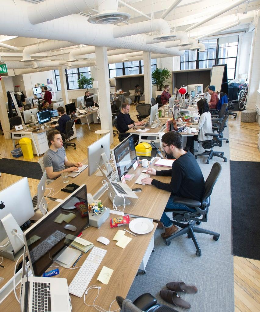 Employees at Shopify Inc. work in their office space in Toronto, Ontario, Canada, on March 13, 2015. Rents for brick-and-beam real estate in the city's east end rose 26 percent to C$20.62 ($16.13) a square foot from 2007 and were up 49 percent in the west end, according to data compiled by CBRE Group Inc. Photographer: Kevin Van Paassen/Bloomberg via Getty Images