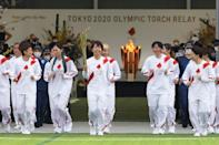 Japanese torchbearer Azusa Iwashimizu (C), a member of Japan women's national football team, leads the torch relay ahead of the Tokyo 2020 Olympic Games in Naraha, Fukushima Prefecture on March 25, 2021.