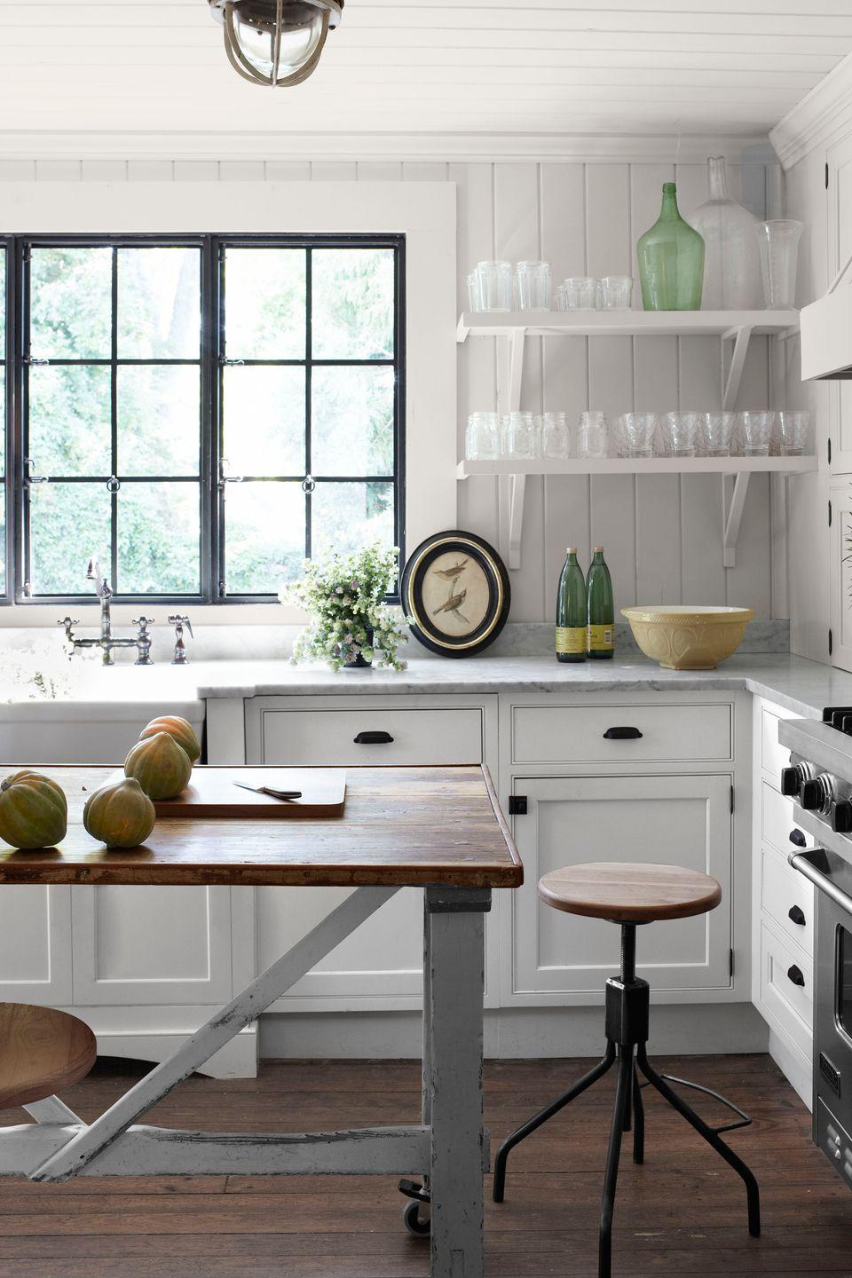 """<p>This antebellum <a href=""""https://www.countryliving.com/home-design/house-tours/g1364/southern-decorating-ideas/"""" rel=""""nofollow noopener"""" target=""""_blank"""" data-ylk=""""slk:Georgia house"""" class=""""link rapid-noclick-resp"""">Georgia house</a> features a late-1800s Belgian butcher's table, now a kitchen island, that still bears traces of newsprint from the table's hardworking industrial days. The homeowners left the Carrara marble counters un-honed to show wear. The walls are painted Country Stove White by Ralph Lauren.</p>"""