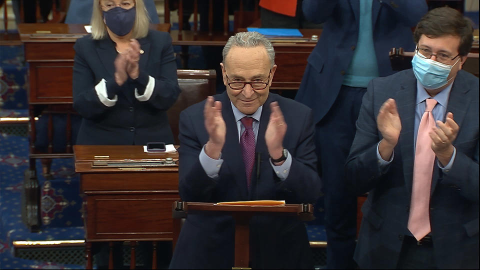 In this image from video, Senate Majority Leader Chuck Schumer of N.Y., leads a round of applause for support staff as he speaks before the final vote on the Senate version of the COVID-19 relief bill in the Senate at the U.S. Capitol in Washington, Saturday, March 6, 2021. (Senate Television via AP)