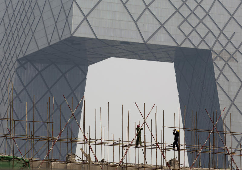 FILE - In this Wednesday, April 2, 2014, file photo, workers install scaffolding on a construction site against the China Central Television building in Beijing. Economists fear a lending bubble in China could threaten the global economy unless the Chinese government shores up its financial system, according to an Associated Press survey. (AP Photo/Andy Wong, File)