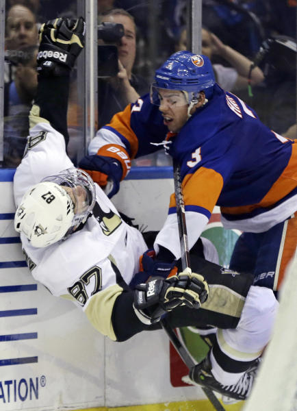 New York Islanders defenseman Travis Hamonic (3) checks Pittsburgh Penguins center Sidney Crosby (87) in the third period of Game 4 of their first-round NHL hockey Stanley Cup playoffs hockey series at Nassau Coliseum in Uniondale, N.Y., Tuesday, May 7, 2013. The Islanders won 6-4. (AP Photo/Kathy Willens)