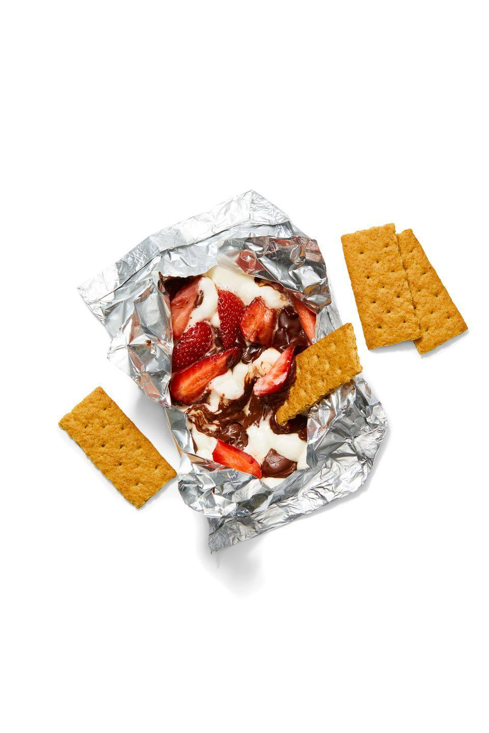 """<p>Grill marshmallows, chocolate chips and strawberries for a gooey, summer-friendly dessert!</p><p><em><a href=""""https://www.goodhousekeeping.com/food-recipes/a27544231/smores-dip-foil-packs-recipe/"""" rel=""""nofollow noopener"""" target=""""_blank"""" data-ylk=""""slk:Get the recipe for S'mores Dip Foil Packs »"""" class=""""link rapid-noclick-resp"""">Get the recipe for S'mores Dip Foil Packs »</a></em></p>"""