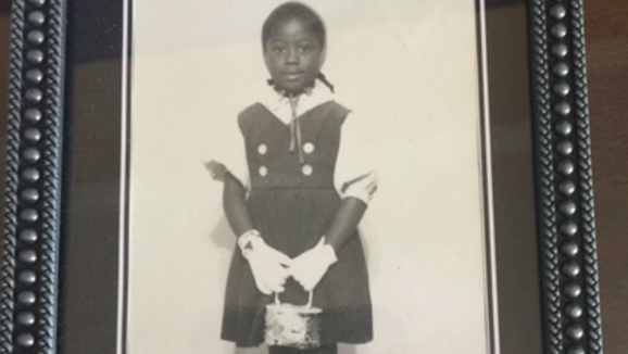 A childhood photo shows a young Trilby Barnes smiling and holding a purse.  (Trilby Barnes/Charlene Dukes)